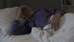 Old man cannot sleep, suffering terrible headache and migraine, insomnia stock video