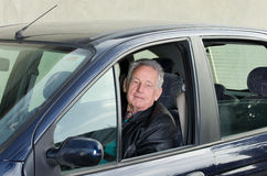 Old man in car. Old man sitting in car and looking in camera through opened window stock photos