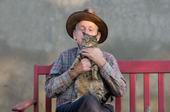 Old man with cat. Old man with hat kissing his cat Royalty Free Stock Images