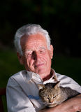 Old man with cat. Old man holding his cat in arms on dark background and dramatic light Royalty Free Stock Photo