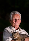 Old man with cat. Old man holding his cat in arms on dark background and dramatic light Royalty Free Stock Image