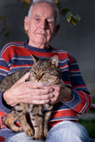 Old man with cat. Old man holding tabby cat in the lap in garden Stock Photo