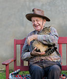 Old man with cat. Old man hugging his cat and laughing Royalty Free Stock Photography