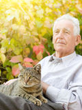 Old man with cat. Senior man cuddle tabby cat in his lap in garden Stock Photos