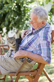 Old man with cat. Senior man with cat in his lap Royalty Free Stock Image