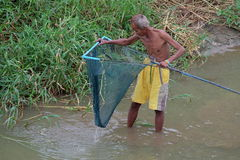 Old man catch some fish, old man find some fish with thailand traditional tool Royalty Free Stock Images