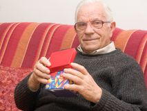 Old man with a Christmas gift Royalty Free Stock Photo