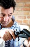 Old man cleaning a gun Royalty Free Stock Photography