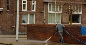 Old man cleaning road, high pressure tool Stock Photos