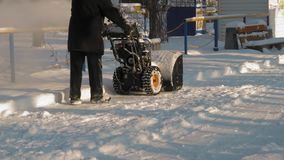 Old Man Clears Snow In City Park. Old Man Removes Snow from the Road In City Park stock footage