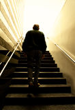 Old man climbing stairs into the light. Man walking upstairs into bright light. Concept of enlightenment royalty free stock photography