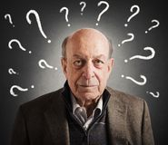 Old man confused. With many question marks Royalty Free Stock Photos