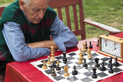 Old man  contemplating and playing chess Royalty Free Stock Photography