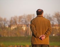 Old Man Contemplating At Promenade. Adult man makeing a pause during walking at promenade and enjoying the view Royalty Free Stock Photos