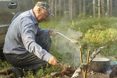 Old man is cooking dinner on campfire Stock Photo