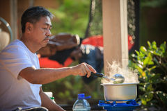 Old man cooking morning food meal in hot pot on lpg gas stove Royalty Free Stock Photos
