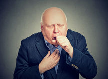 Old man coughing holding fist to mouth Stock Image