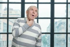 Old man is coughing. stock image