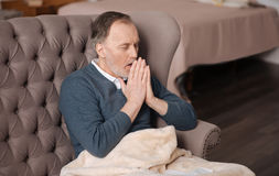 Old man coughing while sitting on couch stock image
