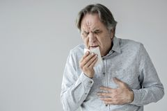 Old man coughing to tissue stock photos