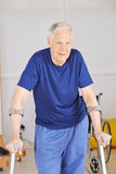 Old man with crutches learning to walk. In rehab after an accident Stock Photos