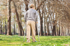 Old man with crutches, walking in the park Royalty Free Stock Images