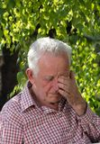 Old man crying in park. Portrait of old man crying on bench in park stock photography