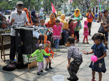 The Old Man and The Dancing Dolls. An old man played a pair of dancing doll in Kota Tua, Jakarta, Indonesia. Popular songs, usually dangdut, were also turned on Royalty Free Stock Image