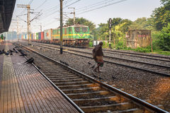 Old man dangerously crosses railway tracks in front of a goods train. Royalty Free Stock Photos