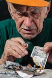 Portrait of an old man, whose financial crisis has destroyed all Stock Photos