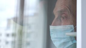 Old man in disposable mask waves hand at plastic window