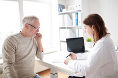Old man and doctor with prescription at hospital Stock Photography