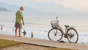 OLd Man Does Morning Exercises on Beach by Bike in Vietnam stock footage