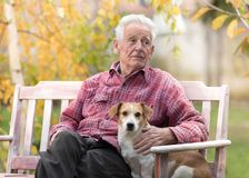 Old man with dog on bench in park. Senior man cuddling cute dog on bench in park with yellow tree in background in autumn. Pet love and care concept. Alternative royalty free stock photos