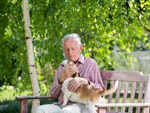 Old man with dog in garden. Old man cuddling dog on bench in garden in spring royalty free stock photo