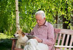 Old man with dog and tablet in garden. Old man with dog sitting on bench in garden and looking at tablet stock photography