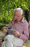 Old man with dog and tablet crying in garden. Sad senior man with his dog sitting on bench in garden, looking at tablet and crying stock photos