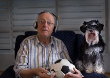 Old man with dog watching football match on tv Royalty Free Stock Photo