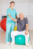 Old man doing back training in nursing home Royalty Free Stock Photo