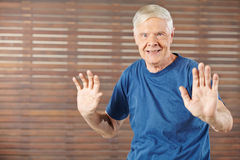 Old man doing gymnastics in fitness center Royalty Free Stock Photography