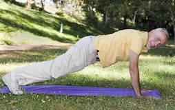 Old man doing push-ups in park Stock Photos