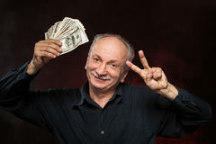 Old man with dollar bills. Lucky old man holding group of dollar bills and fingers in victory sign Stock Photo