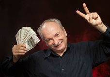 Old man with dollar bills. Lucky old man holding group of dollar bills and fingers in victory sign Royalty Free Stock Images