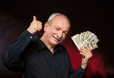 Old man with dollar bills. Lucky old man holding group of dollar bills and show OK sign Stock Photo