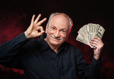 Old man with dollar bills. Lucky old man holding with pleasure group of dollar bills Royalty Free Stock Image