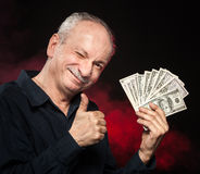 Old man with dollar bills. Lucky old man holding with pleasure group of dollar bills Stock Photography