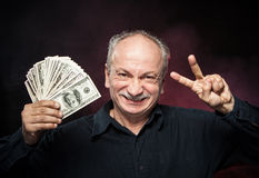 Old man with dollar bills. Lucky old man holding with pleasure group of dollar bills. Focus on face Royalty Free Stock Photo