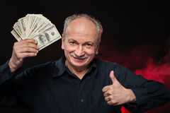 Old man with dollar bills. Lucky old man holding with pleasure group of dollar bills Stock Photos