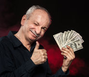 Old man with dollar bills. Lucky old man holding with pleasure group of dollar bills Stock Images