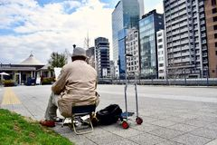 An old man is drawing a picture of Japan Osaka business district office buildings. At the center business district of Osaka Japan, in a sunny day, An old man is stock image